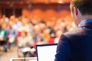 Speaker mit Laptop Richtung Publikum