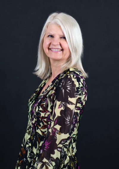 Frau mit blonden Haaren in grünem Kleid mit dunklem Muster